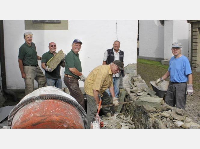 Gut ist die Stimmung beim Arbeitseinsatz des evangelischen Kirchbauvereins an der Kirchenmauer. - Fotos: Goerdt-Heegt