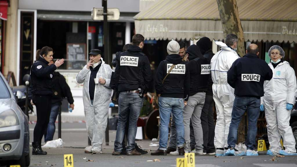 Forensic scientists inspect the Cafe Bonne Biere on Rue du Faubourg du Temple in Paris on November 14, 2015, following a series of coordinated attacks in and around Paris late Friday which left more than 120 people dead. According to witnesses, at least 5 people were killed in the immediate area by attackers wielding automatic rifles. AFP PHOTO / KENZO TRIBOUILLARD