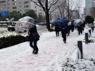 Commuters walk on a snow covered road in Tokyo on January 18, 2016. Heavy snow blanketed Tokyo metropolitan area and transportation systems were paralyzed. AFP PHOTO / YOSHIKAZU TSUNO