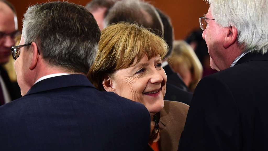 German Chancellor Angela Merkel (C) talks with Hesse&#39s State Premier Volker Bouffier (R)prior to a meeting of cabinet members with the leaders of the country&#39s federal states on January 28, 2016 in Berlin. / AFP / John MACDOUGALL