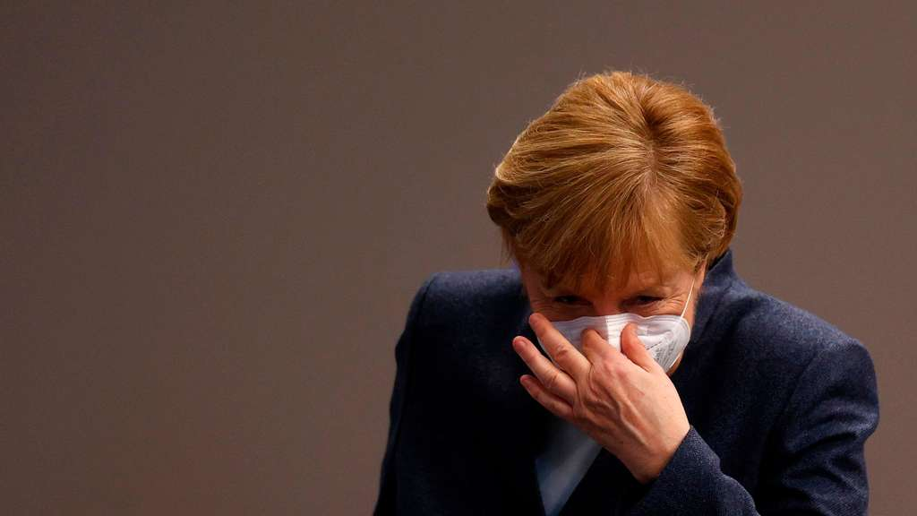 In this file photo taken on December 16, 2020 German Chancellor Angela Merkel puts her face protection mask on after a session of the Bundestag (lower house of parliament) in Berlin, amid the coronavirus Covid-19 pandemic
